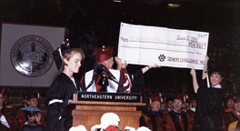 NU President Kenneth Ryder receives the Senior Challenge check from graduate, Kathleen A. Bishop, at the June 1989 commencement ceremony.