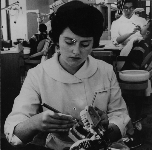 A student from the Forsyth School for Dental Hygienists examining teeth, ca. 1963.